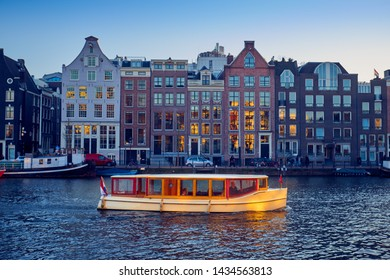 Wooden boat on the canal in Amsterdam during sunset