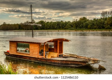 Wooden boat on the Loire Valley in France during an autumn evening day.
