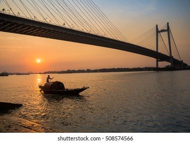 Wooden boat on river Hooghly at sunset with Vidyasagar bridge at the backdrop (silhouette), Photograph shot from Princep ghat, Kolkata, India.