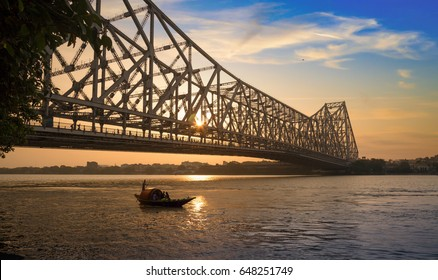 Wooden boat passing the historic Howrah bridge in silhouette at sunrise. Howrah bridge is a cantilever bridge on the river Hooghly and one of the busiest bridge in the world.