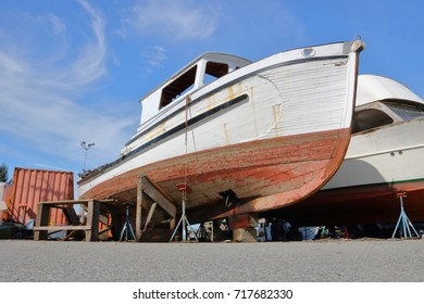 A wooden boat is in for repair and restoration and is mounted on metal jacks for support.