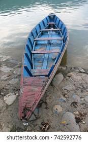 Wooden boat or Sampan abandoned at the lake sore