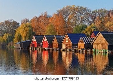 Wooden boathouses at lake Muritz (Müritz) near Robel (Röbel) with trees autumn foliage in evening light in Mecklenburg-Vorpommern, Germany. Autumn landscape.