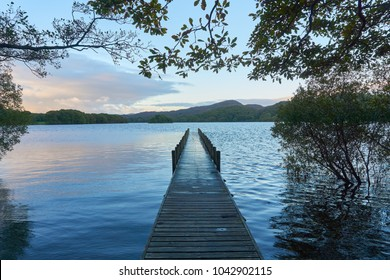A wooden boating jetty surrounded by overhanging trees juts out into Coniston Water, The Lake District, UK
