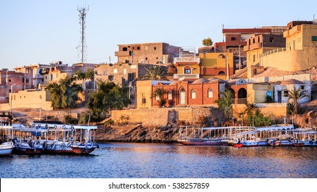 Wooden boats carrying passengers docked along the Nile River at the Temple of Philae in Aswan, Egypt, North Africa