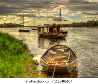 Wooden boats on the Loire Valley in France during an autumn evening day.