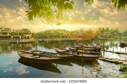 Wooden boats on the Thu Bon River in Hoi An Ancient Town,  Vietnam. Yellow old houses on waterfront reflected in river. Vietnam