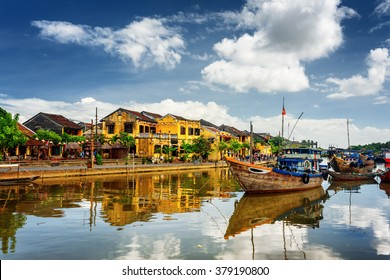 Wooden boats on the Thu Bon River in Hoi An Ancient Town (Hoian), Vietnam. Yellow old houses on waterfront reflected in river. Hoi An is a popular tourist destination of Asia.