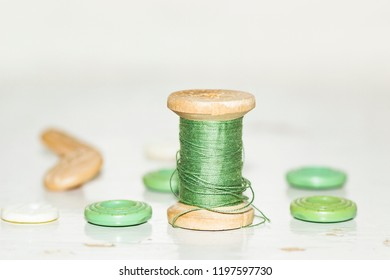 wooden bobbin with green threads and buttons