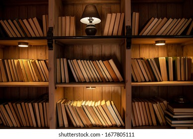 Wooden bookcase with books. On the shelves there are many different books illuminated by warm light. Home library.