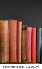 Wooden bookshelf with row of battered old vintage books standing upright.  Blank spines and chalkboard background provide copy space.