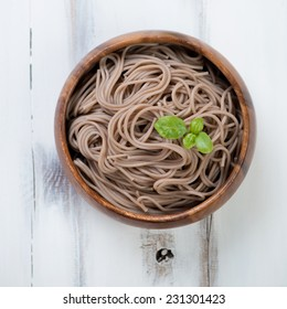 Wooden bowl with buckwheat soba noodles and green basil