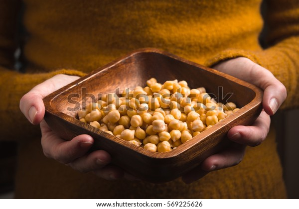 Wooden bowl with chickpeas in the hands horizontal