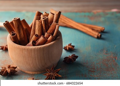 Wooden bowl with cinnamon sticks and anise on table