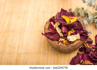 Wooden bowl and colored petals, decorated with branches on wooden background.