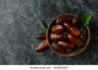 Wooden bowl of dates on black smokey background