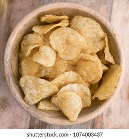 Wooden bowl filled with chips viewed from above.