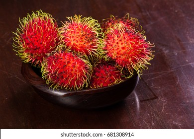 wooden bowl filled with rambutan placed on a wooden table, Rambutan is a sweet tropical fruit.