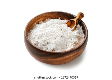 Wooden bowl with flour and flour spoon. Rice or wheat flour isolated on white background.