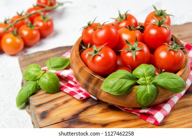 Wooden bowl with fresh ripe cherry tomatoes and basil leaves on a table with red checkered towel, healthy food