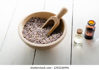 Wooden bowl full of dried lavender flower buds with scoop, next to  glass vials filled with oils on white painted wood plank table..