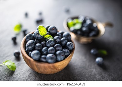 Wooden bowl full of fresh blueberries with herbs.