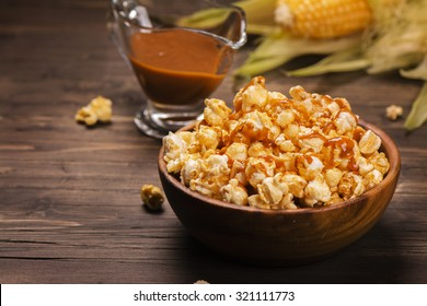Wooden bowl full of sweet caramel popcorn with caramel sauce and corncobs over rustic table. Vintage style. Selective focus