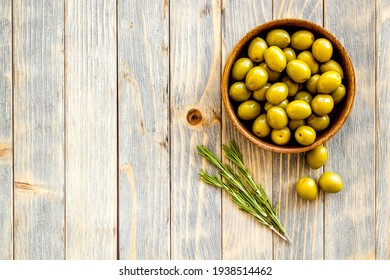 Wooden bowl with green olives. Overhead view, space for text