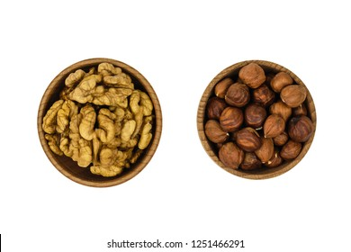 Wooden bowl with hazelnuts and wallnuts isolated on white background. The view from the top.
