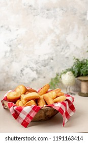 Wooden Bowl Lined with Red and White Checked Tablecloth with Homemade Cornbread Muffins, Slices and Sticks