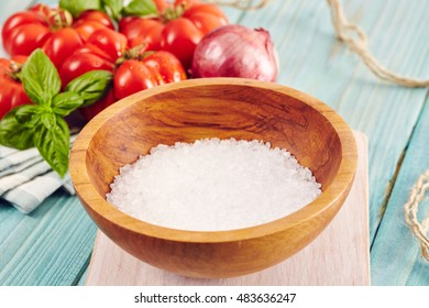 a wooden bowl with marine salt crystals surrounded by tomatoes and onion on an aquamarine wooden table