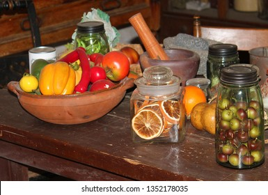 A wooden bowl is on a rustic wooden table with glass jars and fruit