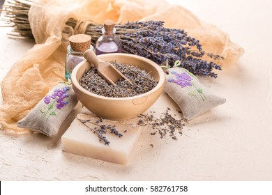 Wooden bowl with petals of lavender bottles of aromatic oil and salt sachets with embroidery, homemade soap and dried lavender bouquet