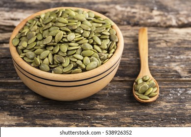 Wooden bowl and pumpkin seeds on wooden background