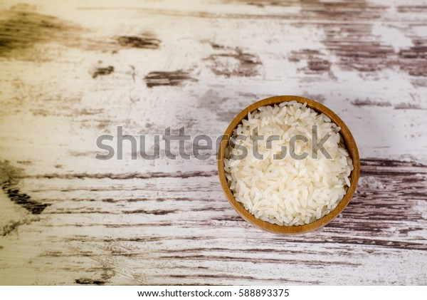 Wooden bowl with rice on vintage boards.