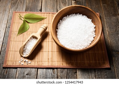 Wooden bowl with salt and accessories on natural background. Selective focus.