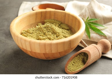 Wooden bowl and scoop with hemp protein powder on table