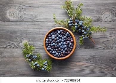 Wooden bowl with seeds of juniper. Juniper branch with berries. Juniper berries in a bowl with a sprig.