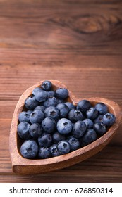 Wooden bowl in the shape of heart with blueberries standing on brown rustic background. Healthy food