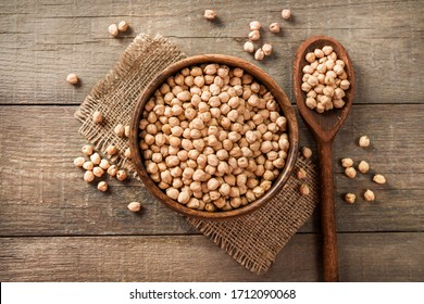 Wooden bowl and wooden spoon full of chickpeas on wooden background. Top view.