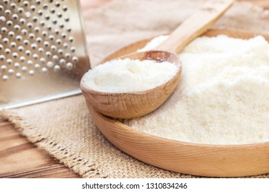 Wooden bowl and wooden spoon with grated parmesan and grater on wooden background.