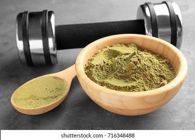 Wooden bowl and spoon of hemp protein powder on table