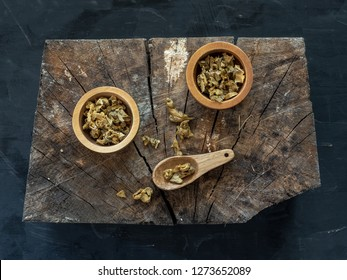 Wooden bowl and spoon of propolis granules on piece of wood. Flat lay.