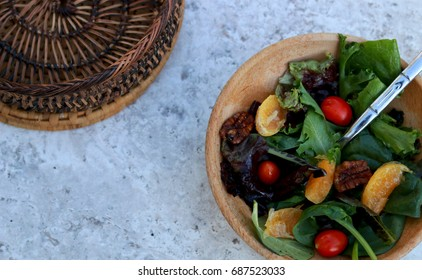 wooden bowl spring salad with mandarin slices