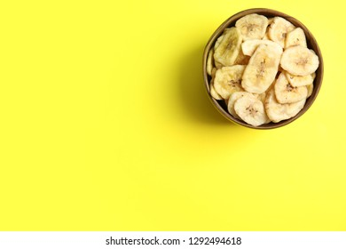 Wooden bowl with sweet banana slices on color background, top view with space for text. Dried fruit as healthy snack