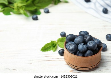 Wooden bowl with tasty blueberries on white table, space for text