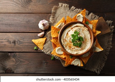Wooden bowl of tasty hummus with chips, parsley and garlic on table