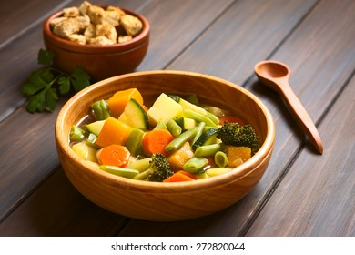 Wooden bowl of vegetable soup made of zucchini, green bean, carrot, broccoli, potato and pumpkin, croutons in back, photographed with natural light (Selective Focus, Focus one third into the soup)