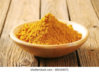 wooden bowl with yellow curry powder