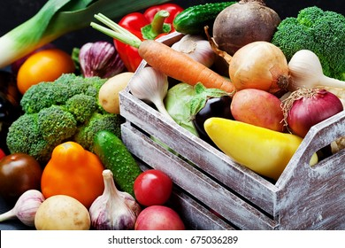 Wooden box with autumn harvest farm vegetables and root crops. Healthy and organic food background.